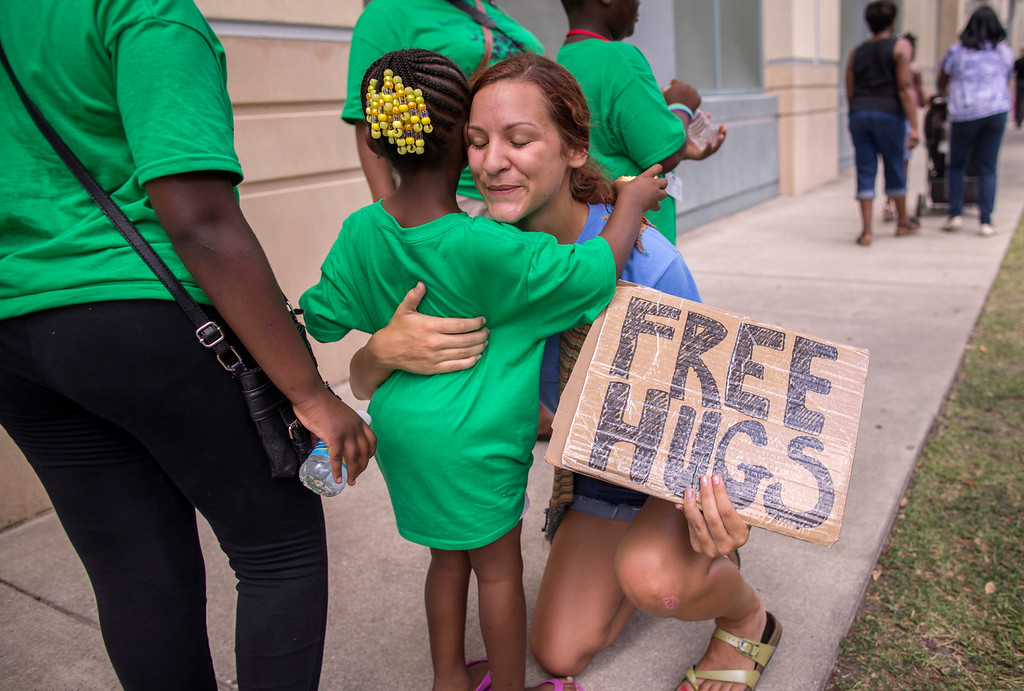 . Sharry Schuller of Charleston give out free hugs to anyone who wants one while visiting the memorial in front of the  Emanuel AME Church, Saturday, June 20, 2015, in Charleston, S.C. (AP Photo/Stephen B. Morton)
