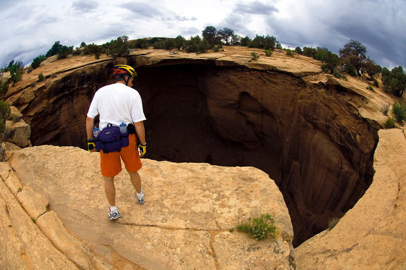 Peering over the void created by the Gemini Bridges formation outside of Canyonlands, UT