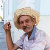 CIENFUEGOS. CUBA. OLD CUBAN MAN WITH HAT SMOKES HIS CIGAR.