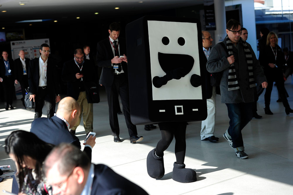 . A hostess wearing a mobile phone costume walks at the 2013 Mobile World Congress in Barcelona on February 26, 2013. The 2013 Mobile World Congress, the world\'s biggest mobile fair, is held from February 25 to 28 in Barcelona.  JOSEP LAGO/AFP/Getty Images