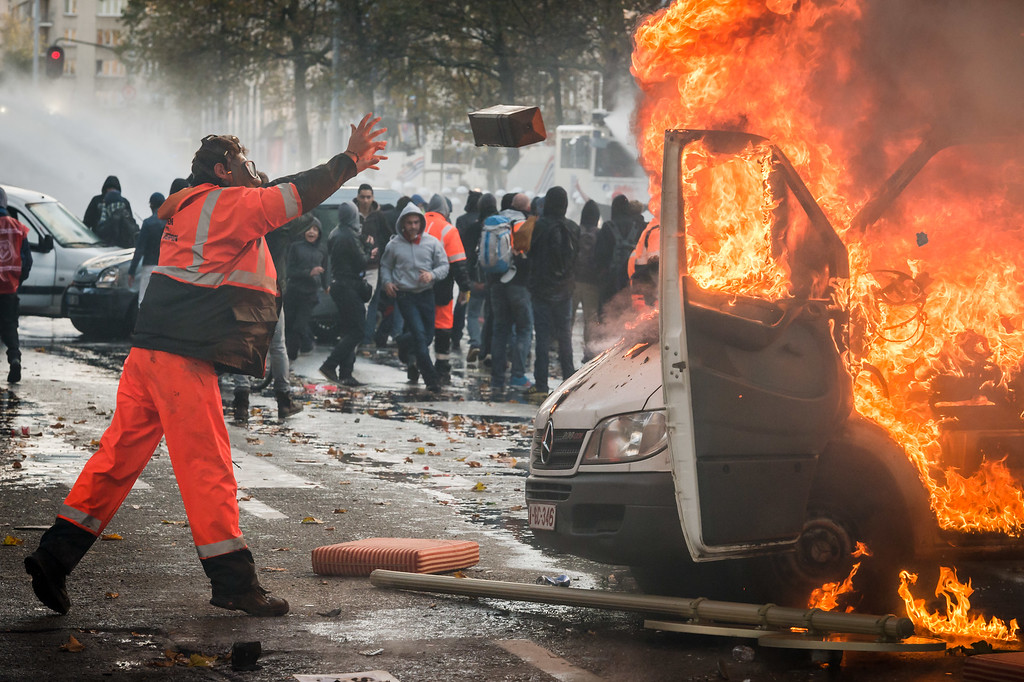 . A protestor wearing a gas mask throws a metal box into a burning car during a national trade union demonstration in Brussels, Thursday Nov. 6, 2014. (AP Photo/Geert Vanden Wijngaert)