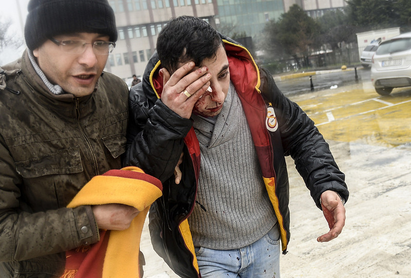 . A Turkish protester escorts a fellow demonstrator after he was wounded in clashes with riot policemen outside Okmeydani Hospital in Istanbul on March 11, 2014. Violent protests erupted between police and hundreds of protesters outside the hospital where a teenager, who had fallen into a coma after being hit by a tear gas canister during mass anti-government protests last year, died. (BULENT KILIC/AFP/Getty Images)