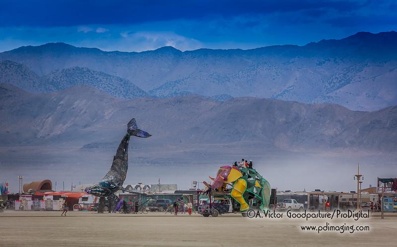 An elephant art car passes Space Whale.