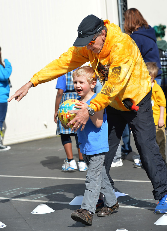 . Jim Turnbull, an adaptive Physical education instructor for the Contra Costa County Office of Education\'s East County Student Programs, helps James, 5, of Antioch, get ready to shoot a basketball during a Special Olympics basketball skills event at Turner Elementary School in Antioch, Calif., on Friday March 8, 2013.  (Dan Rosenstrauch/Staff)