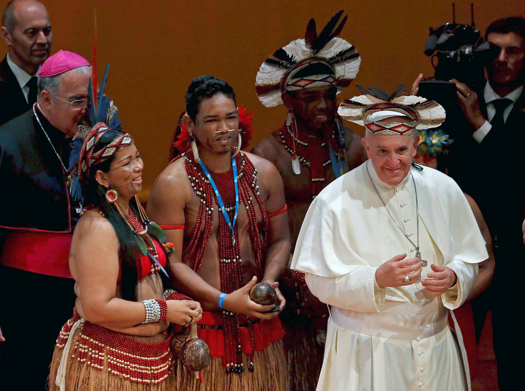 . Pope Francis wears an indigenous headdress given to him by Ubirai Matos from the Pataxo tribe, fourth from left, after the pontiff spoke at Rio\'s Municipal Theater to an audience mostly made up of Brazil\'s political, business and cultural elite in Rio de Janeiro, Brazil, Saturday, July 27, 2013. Pope Francis is on the sixth day of his trip to Brazil where he will attend the 2013 World Youth Day in Rio. (AP Photo/Monica Imbuzeiro, Agencia O Globo)