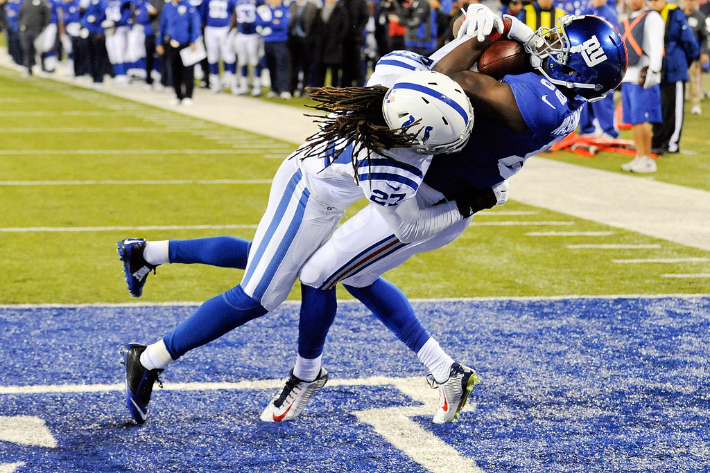 . New York Giants wide receiver Corey Washington, right, catches a pass for a touchdown as he is defended by Indianapolis Colts\' Josh Gordy (27) during the second half of an NFL football game Tuesday, Nov. 4, 2014, in East Rutherford, N.J. (AP Photo/Bill Kostroun)