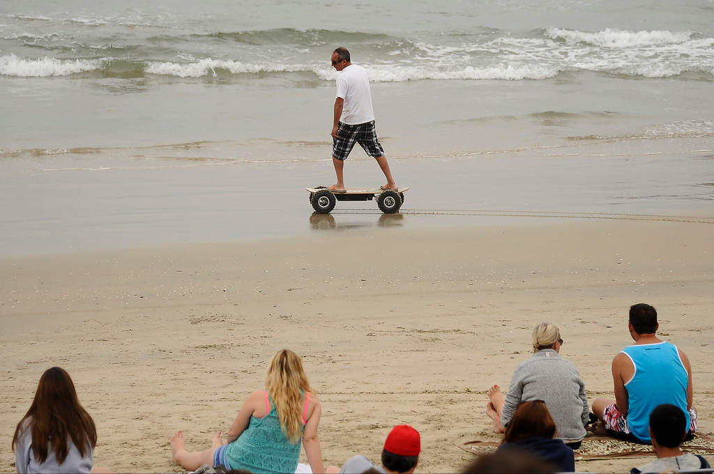 . A man cruses buy on a electric skateboard during the 2013 Vans US Open of Surfing Sunday at Huntington Beach CA. July 27,2013. Photo by Gene Blevins/LA DailyNews