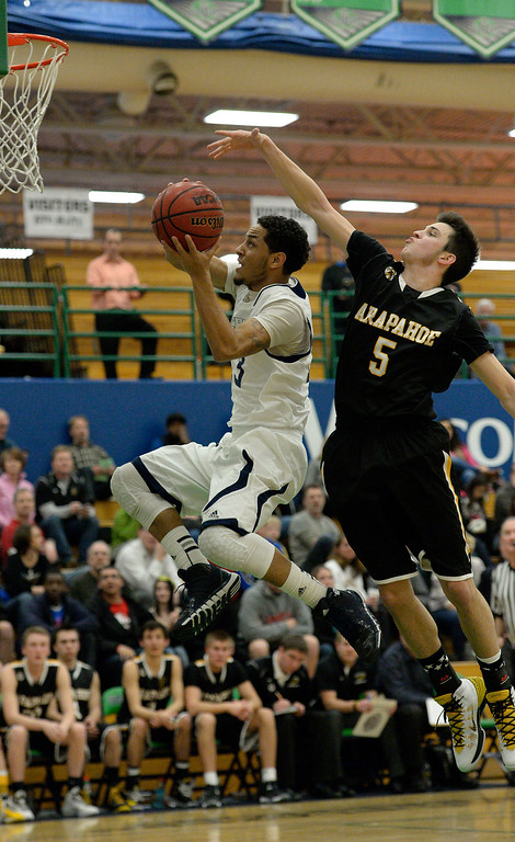 . AURORA, CO - FEBRUARY 12: Overland Khalil Jenkins (13) flies through the air on his way to a score past Arapahoe James Dalrymple (5) during their 5A basketball game February 12, 2014 in Aurora. Overland defeated Arapahoe 72-65. (Photo by John Leyba/The Denver Post)