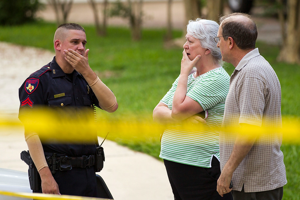 . People stand with a law enforcement officer near the scene of a shooting Wednesday, July 9, 2014, in Spring, Texas. A Harris County Sheriff\'s Office statement says precinct deputy constables were called to the house about 6 p.m. Wednesday and found two adults and three children dead. Another child later died at a hospital. (AP Photo/Houston Chronicle, Brett Coomer)