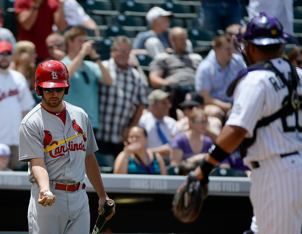 . Colorado Rockies catcher Wilin Rosario (20) toss the baseball to the bat boy. The ball belongs to St. Louis Cardinals starting pitcher Marco Gonzales (56) who got his first major league hit, a double to center field off of Colorado Rockies starting pitcher Yohan Flande (58) in the third inning June 25, 2014 at Coors Field. (Photo by John Leyba/The Denver Post)