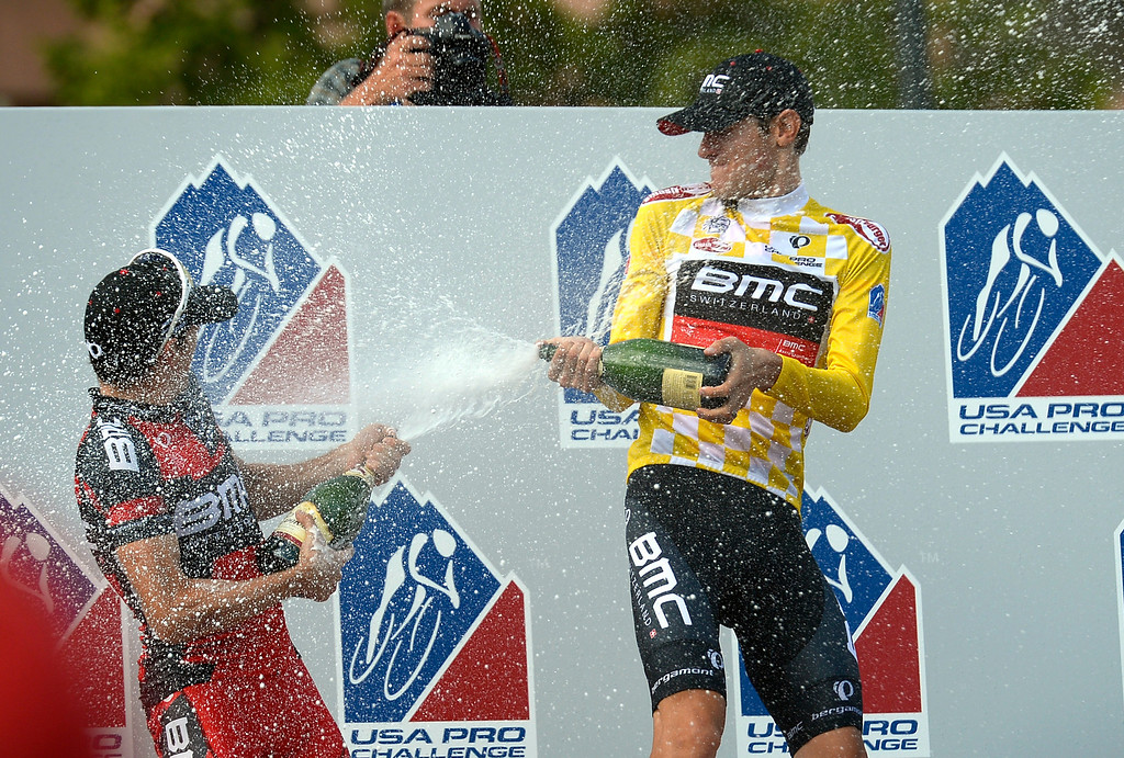 . Aspen\'s Tejay Van Garderen of BMC Racing pours champagne over his teammate after winning the team competition with a time of 68:00:42 in the 3rd annual Pro Cycle Challenge August 25, 2013. The final stage took place in downtown Denver winding through the streets and finishing near the state Capitol. (Photo by John Leyba/The Denver Post)