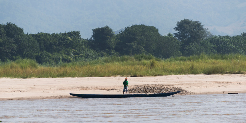 Man standing on shoreline of River Mekong, Lai Ngao, Wiang Kaen District, Chiang Rai Province, Thailand