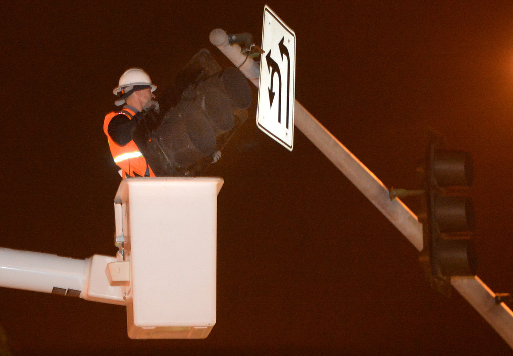 . A city worker removes a signal light that was dangling from its wires at the intersection of Beach Booulevard and Lambert Road in La Habra on Friday March 28, 2014. (Staff Photo by Keith Durflinger/Whittier Daily News)
