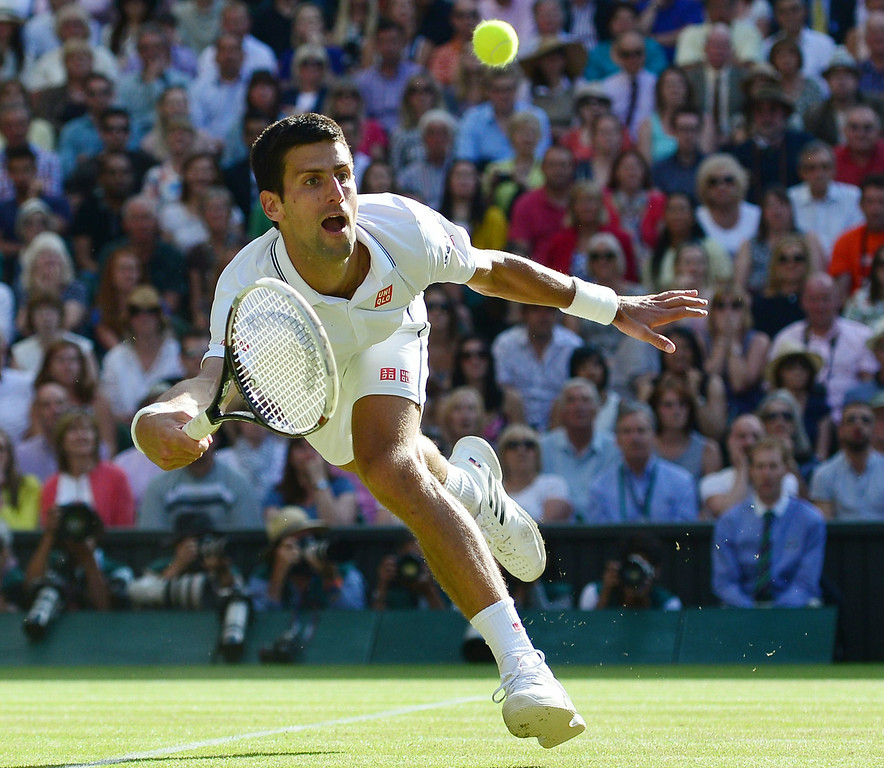 . Serbia\'s Novak Djokovic reaches out for the ball before falling down during his men\'s singles final match against Switzerland\'s Roger Federer on day thirteen of  the 2014 Wimbledon Championships at The All England Tennis Club in Wimbledon, southwest London, on July 6, 2014.    CARL COURT/AFP/Getty Images