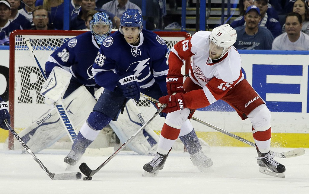 . Detroit Red Wings center Riley Sheahan (15) reaches for the puck in front of Tampa Bay Lightning defenseman Matt Carle (25) during the second period of Game 7 of a first-round NHL Stanley Cup hockey playoff series Wednesday, April 29, 2015, in Tampa, Fla. (AP Photo/Chris O\'Meara)