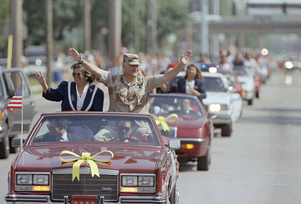 Description of . Gen. H. Norman Schwarzkopf and his wife Brenda wave from a motorcade during a tribute to the men and women of Operation Desert Storm in Tampa, Florida, Sunday, May 5, 1991. (AP Photo)