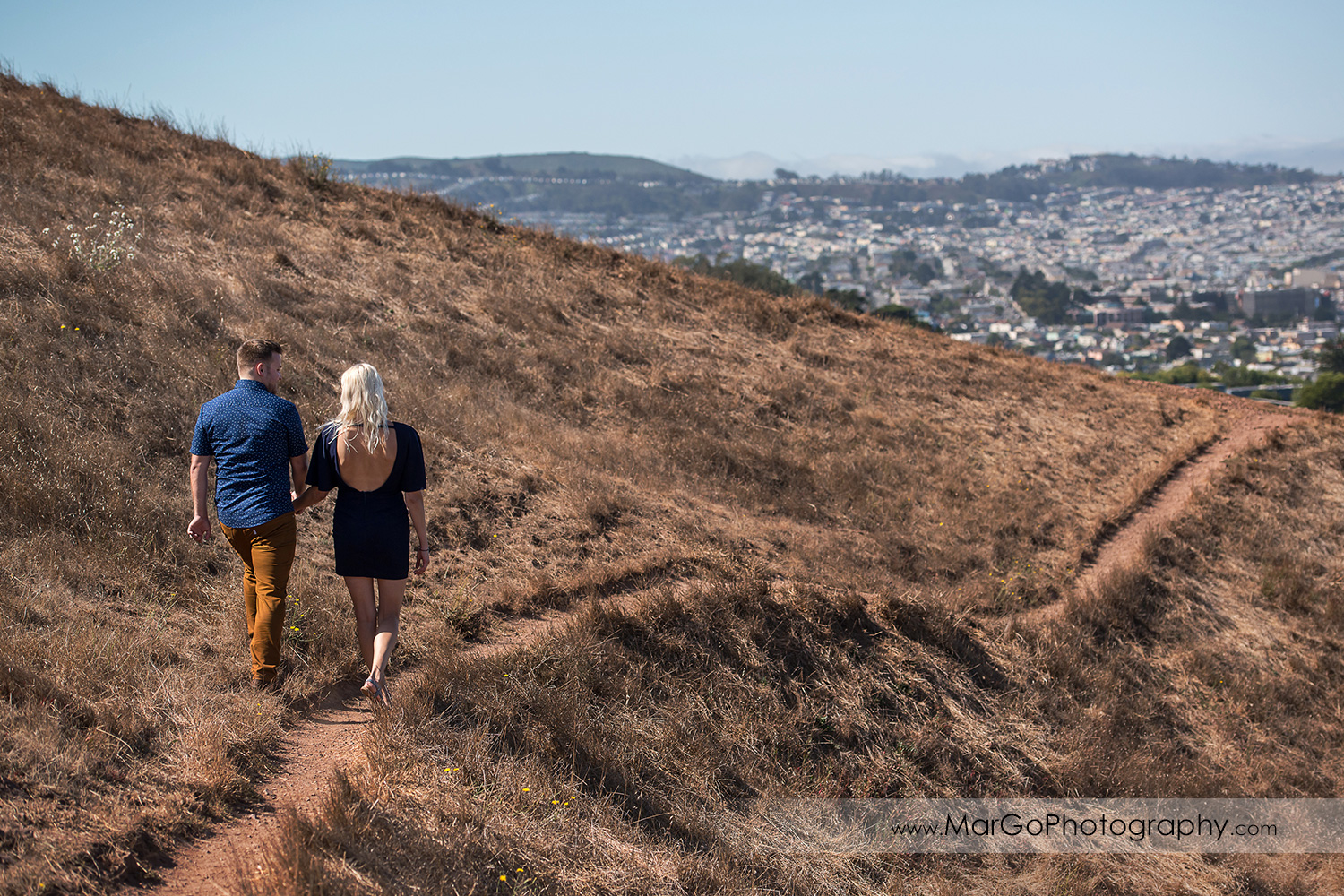 engagement session at Bernal Heights in San Francisco - couple walking on the hill with SF view