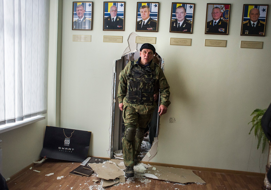 . Crimean self-defense forces member walks in the Ukrainian navy headquarters in Sevastopol, Crimea, Wednesday, March 19, 2014. C (AP Photo/Andrew Lubimov)
