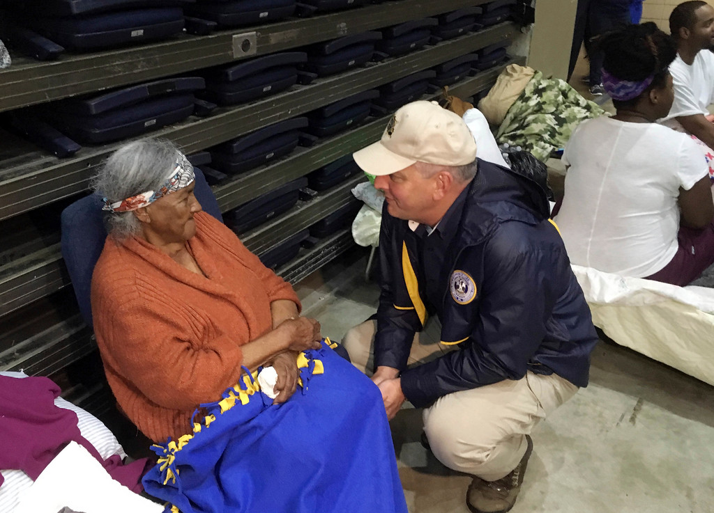 . Louisiana Gov. John Bel Edwards, right, confers with a flood refugee in the Lake Charles Civic Center shelter, in Lake Charles, La., Tuesday, Aug. 29, 2017. Edwards spent some time speaking with a number of the evacuees, as the facility readies for another bout of rain from Tropical Storm Harvey. (AP Photo/Jeff Amy)