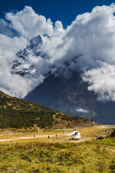 Sherpas Stand Around Cargo Offloaded From A Helicopter At A High Altitude Airstrip Near Mount Everest, Nepal