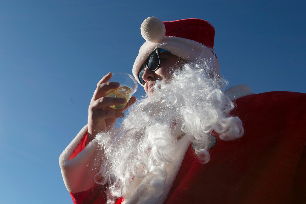 . A man dressed as Santa Claus drinks a beer as he and others participate in SantaCon on a rooftop bar, Saturday, Dec. 13, 2014, in New York.   SantaCon organizers retained lawyer Norman Siegel  last week as part of an effort to tame the excesses of the daylong party.  Siegel said the government cannot ban SantaCon. But he said the government can reasonably regulate the event. (AP Photo/John Minchillo)