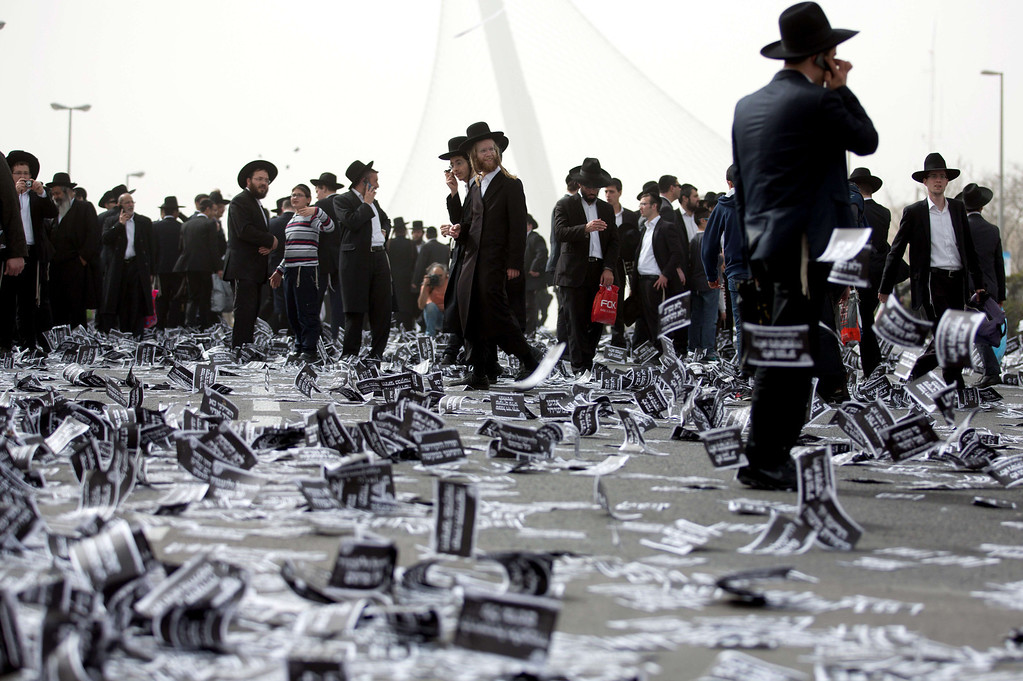 . Ultra Orthodox Jews walk past flying leaflets as they gather along with hundreds of thousands on March 2, 2014, in Jerusalem to demonstrate against any plans to make them undergo military service. The protests were sparked by cuts in government funding to Jewish theological seminaries, or yeshivas, and a planned crackdown on young ultra-Orthodox men seeking to avoid Israel\'s compulsory military draft.   MENAHEM KAHANA/AFP/Getty Images