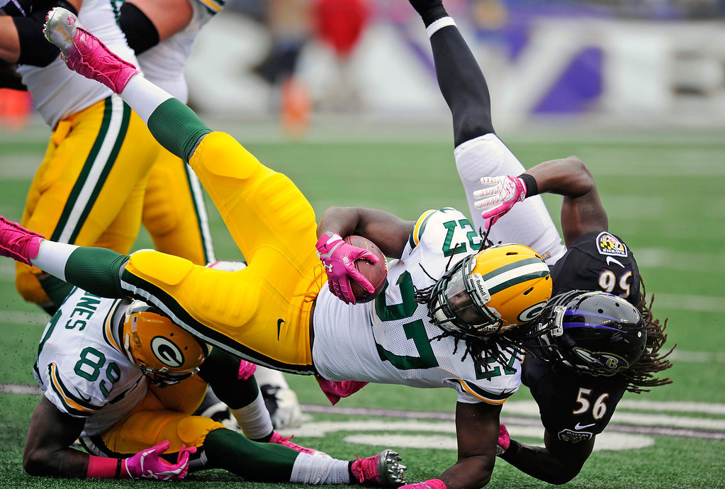 . Green Bay Packers running back Eddie Lacy (27) is knocked off his feet by Baltimore Ravens inside linebacker Josh Bynes (56) during the first half of an NFL football game in Baltimore, Sunday, Oct. 13, 2013. (AP Photo/Nick Wass)