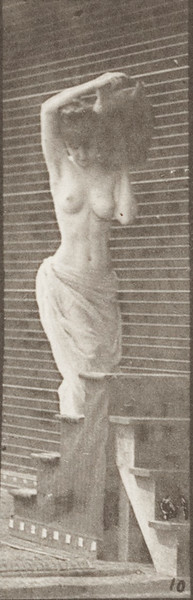 Semi-nude woman turning and ascending stairs holding a water jar on her left shoulder