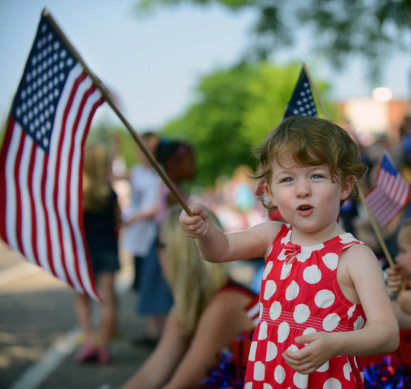 . Three-year-old Lena Spirn holds a flag as she enjoys the St. Anthony Park parade. The Minneapolis resident joined hundreds of other spectators and participants in the long-running Fourth in the Park celebration. (Pioneer Press: Chris Polydoroff)