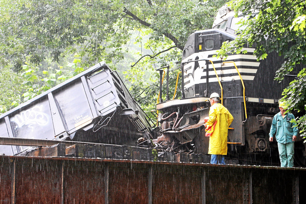 . Workers look over as two cars go off a bridge into the Brandywine Creek following a train derailment in Valley, Chester County, on Monday, July 8, 2013.