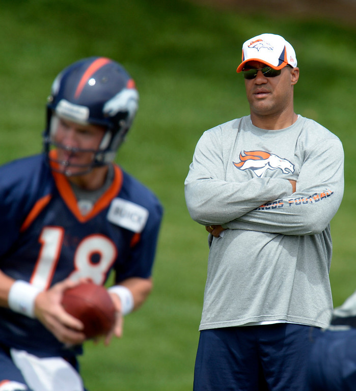 . Eric Studesville, running backs coach of the Denver Broncos  looks on as Peyton Manning (18) runs the play during mini camp June 12, 2013 at Dove Valley. (Photo By John Leyba/The Denver Post)