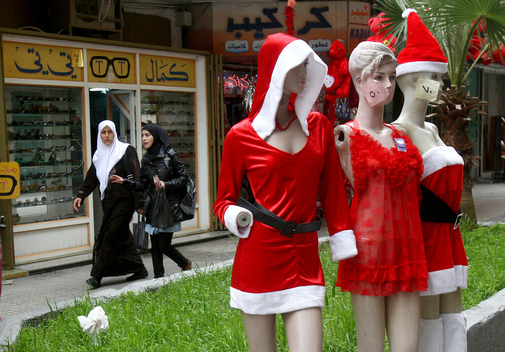 . Palestinian women walk behind mannequins decorated for Valentine\'s Day, outside a shop in the West Bank city of Nablus, Thursday, Feb. 14, 2012. Valentine\'s Day is a festival of romantic love and is celebrated in many countries over the world by giving cards, flowers or gifts to spouses or partners. (AP Photo/Nasser Ishtayeh)