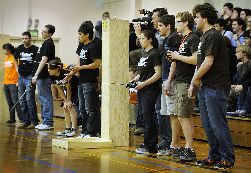 """. TEeam Gym Rats, left, with their remote  robot controls competing against Team, How to Train Your Blimp during this year\'s 28th Annual ME72 Engineering Design Contest, \""""Sponge Wars Attack of the Drones\"""" at Caltech Brown Gym Tuesday, March 13, 2013. Mechanical Engineering 72 competition features teams maneuvering kitchen sponges into a goal with a pair of autonomous robotic vehicles � and preventing opposing teams from doing the same. Six teams  competed head-to-head in a series of rounds. The team with the most points at the end of each heat wins. The victors earn the admiration of the crowds in the stands and are honored with the ME-72 trophy. (Photo by Walt Mancini/SXCity)"""