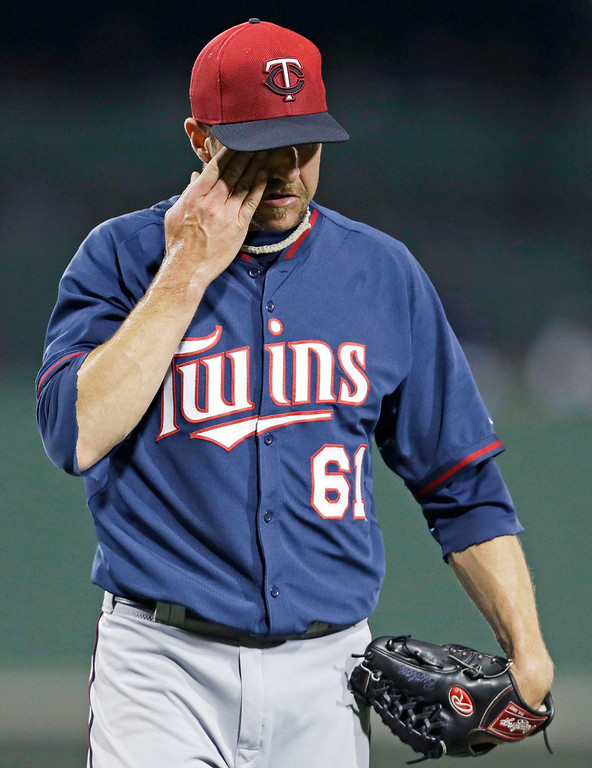 . Minnesota Twins relief pitcher Jared Burton (61) walks of the mound at the end of the seventh inning, after giving up the go-ahead run. (AP Photo/Gerald Herbert)