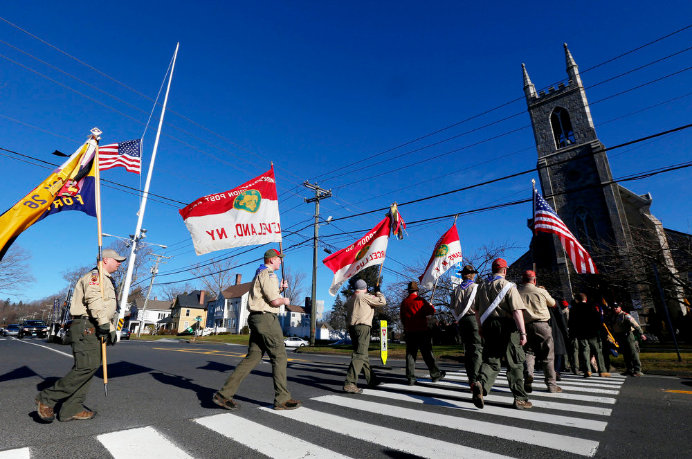 . People wearing Boy Scouts of America uniforms carry flags as they walk toward Trinity Episcopal Church before funeral services for Benjamin Andrew Wheeler, Thursday, Dec. 20, 2012, in Newtown, Conn. Wheeler, 6, died when the gunman, Adam Lanza, walked into Sandy Hook Elementary School in Newtown, Dec. 14, and opened fire, killing 26 people, including 20 children, before killing himself. (AP Photo/Julio Cortez)