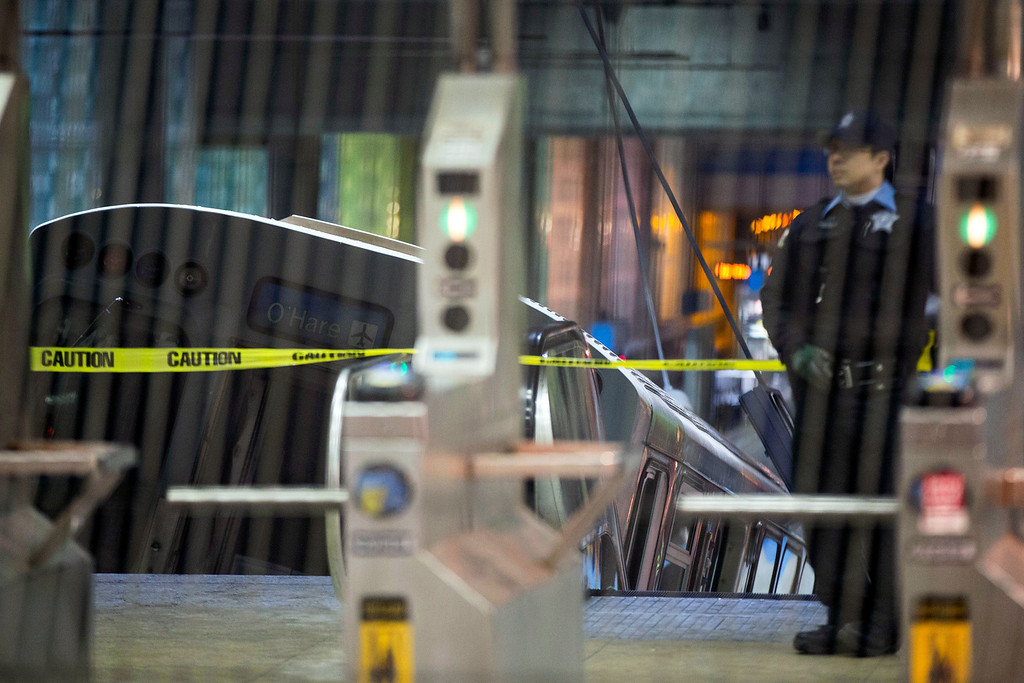 . A police officer stands near a Chicago Transit Authority train car that derailed at the O\'Hare Airport station early Monday, March 24, 2014, in Chicago. More than 30 people were injured after the eight-car train plowed across a platform and scaled an escalator at the underground station. (AP Photo/Andrew A. Nelles)