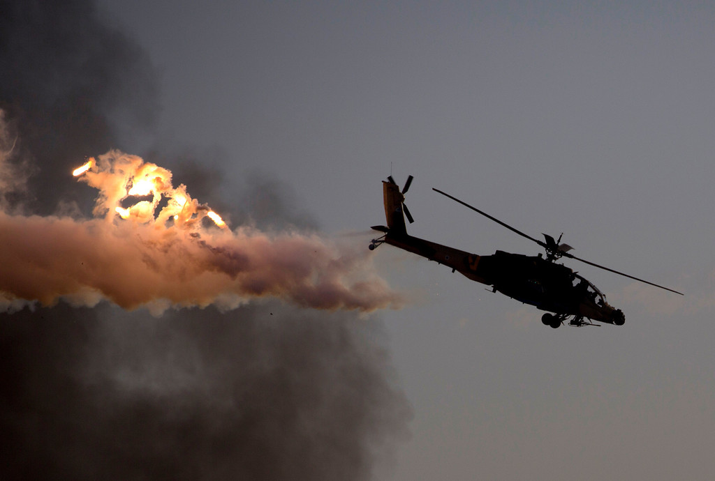 . An Israeli Air Force Apache helicopter releases flares during an aerobatic display at a graduation ceremony for new pilots in the Hatzerim air force base near the city of Beersheba, southern Israel, Thursday, Dec. 26, 2013. (AP Photo/Ariel Schalit)
