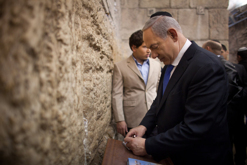 Description of . Israeli Prime Minister Benjamin Netanyahu writes a note to place in the Western Wall, Judaism holiest site, on January 22, 2013 in Jerusalem, Israel. Israel's general election voting has begun today as polls show Netanyahu is expected to return to office with a narrow majority. (Photo by Uriel Sinai/Getty Images)