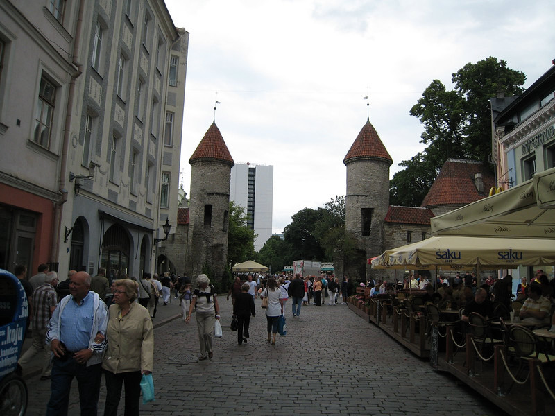 Street scene in Tallinn and towers of the ancient old town wall