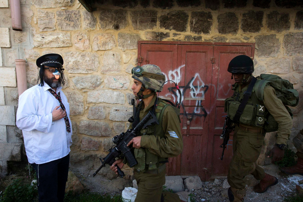 . A Jewish settler, dressed in costume, stands near Israeli soldiers as they guard during a parade for the holiday of Purim in the West Bank city of Hebron February 24, 2013. Purim is a celebration of the Jews\' salvation from genocide in ancient Persia, as recounted in the Book of Esther. REUTERS/Ronen Zvulun