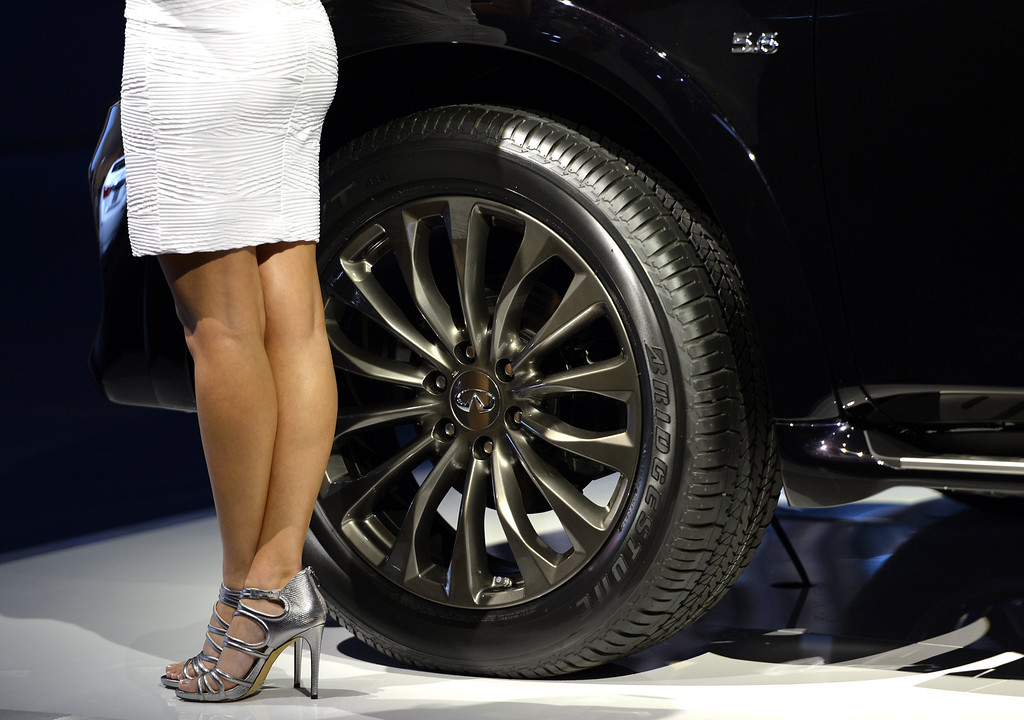 . A model stands next to a Infinity SUV on display during the first press preview day at the 2014 New York International Auto Show  April 16, 2014  at the Jacob Javits Center in New York. The auto show is open to the public April 18-27. AFP PHOTO / Timothy A. Clary/AFP/Getty Images