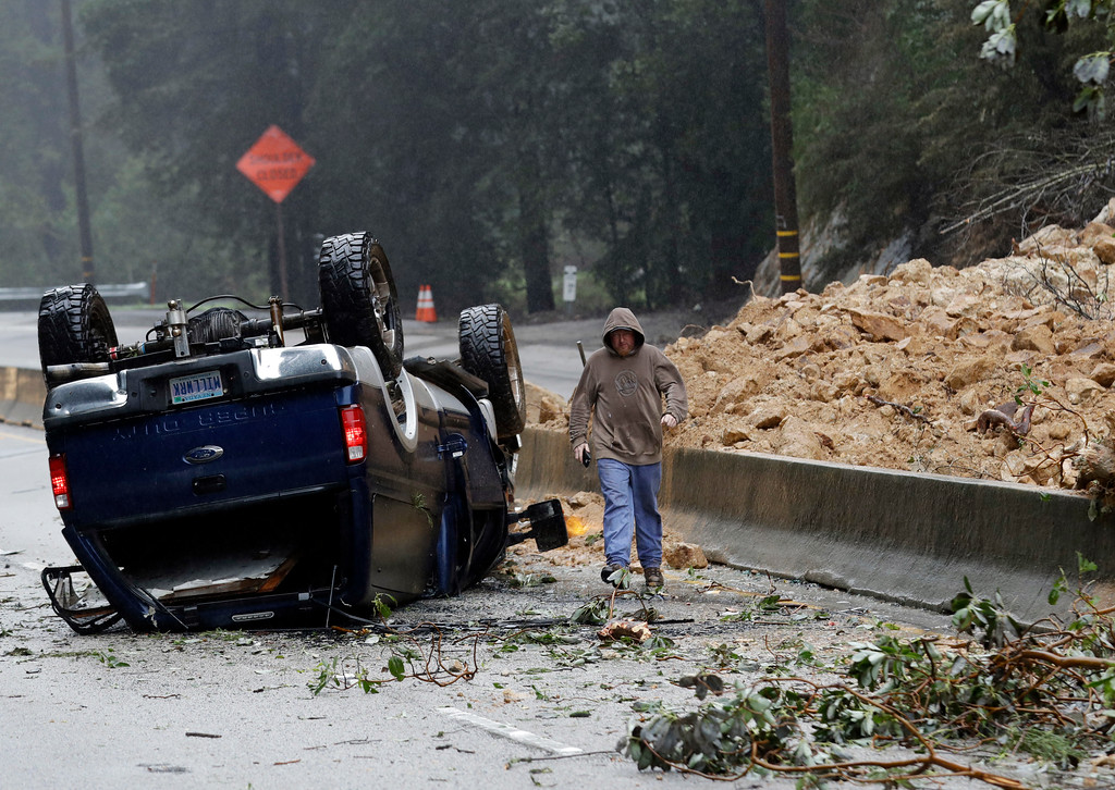 . A tow truck operator walks past an overturned vehicle on the south bound lane next to a mudslide which caused the complete closure of Highway 17 north Tuesday, Feb. 7, 2017, south of Santa Cruz, Calif. Flash flood watches are in place for parts of Northern California down through the Central Coast as heavy rains swamp roads and threaten to overtop rivers and creeks. (AP Photo/Marcio Jose Sanchez)