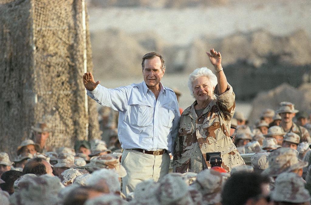. Pres. George H. W. Bush, left, and First Lady Barbara Bush wave to U.S Marines at the desert encampment during a thanksgiving visit, Thursday, Nov. 22, 1990, Saudi Arabia. (AP Photo/Scott Applewhite)