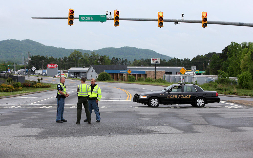 . Cobb County Police block off Old US 41 Highway after an early morning workplace shooting at the Airport Road FedEx facility Tuesday April 29, 2014, in Kennesaw, Ga. (AP Photo/Jason Getz)