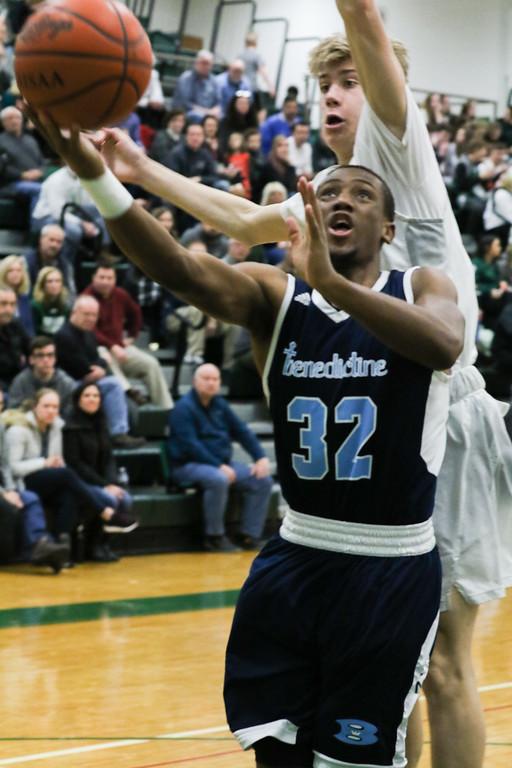 . 2018 - Basketball - Benedictine at Lake Catholic.  Benedictine defeated Lake Catholic 63-56.  Benedictine\'s Chris Jefferson (32) puts up a layup under pressure from  Lake Catholic\'s Luke Frazier (5).