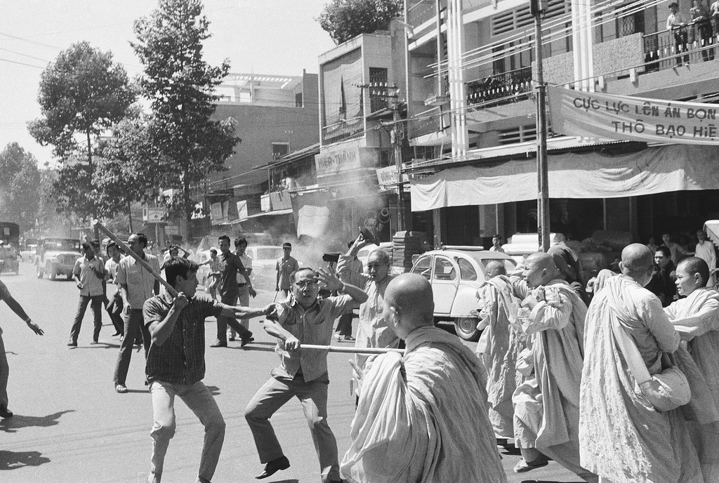. Two stick-wielding plainclothes policemen fight South Vietnamese Buddhist nuns in Saigon, Sunday, Jan. 26, 1975 during anti government demonstration. Officer (left) warns comrade that nun (background) is about to hit him with sandal. Melee occurred following political convention at pagoda. (AP Photo/Nguyen Tu A)