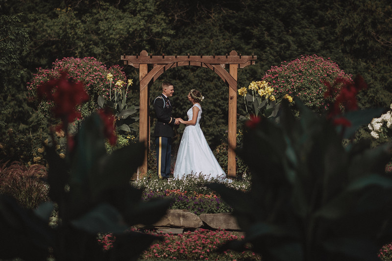 The bride and groom pose under a garden arbor surrounded by flowers.