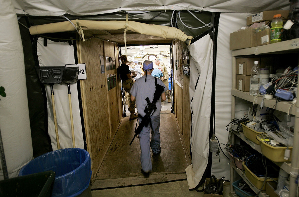 . Major Hans Bakken, a U.S. Army neurosurgeon from Decorah, Iowa, enters a surgical ward with his unloaded rifle on his back March 16, 2006 in Balad, Iraq. Balad was one of the primary hospitals for troops and civilians injured in the conflict in Iraq. (Photo by Chris Hondros/Getty Images)