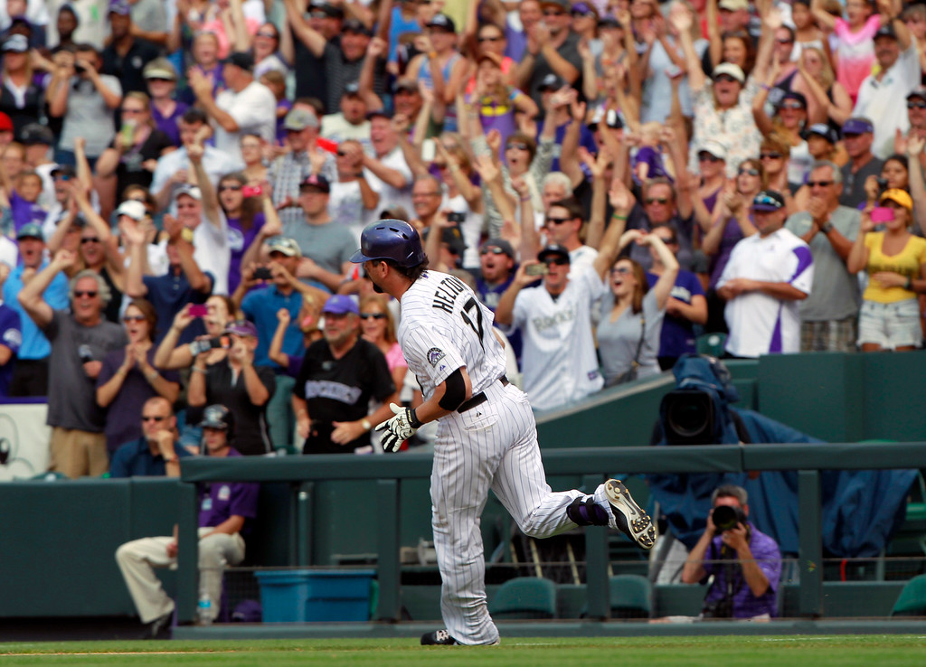 . Fans cheer as Colorado Rockies\' Todd Helton rounds first base on the way to second base with a double against the Cincinnati Reds in seventh inning of a baseball game in Denver on Sunday, Sept. 1, 2013. The hit was the 2,500th in Helton\'s career. (AP Photo/David Zalubowski)