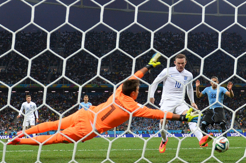 . England\'s forward Wayne Rooney (L) scores against Uruguay\'s goalkeeper Fernando Muslera (L) during a Group D football match between Uruguay and England at the Corinthians Arena in Sao Paulo during the 2014 FIFA World Cup on June 19, 2014.  (BEN STANSALL/AFP/Getty Images)
